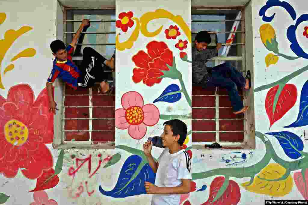 """The Castle"" was opened to refugees in 2013. These children are playing on the bars of the former prison cell windows."