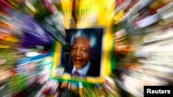 Плакат с первым чернокожим президентом ЮАР Нельсоном Манделой среди цветов