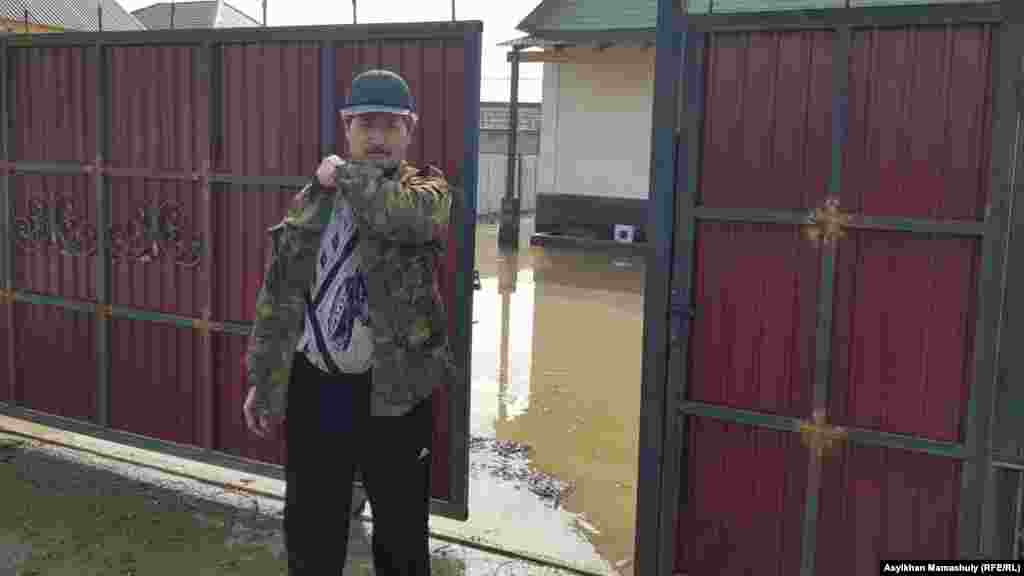 Житель поселка на фоне затопленного двора.