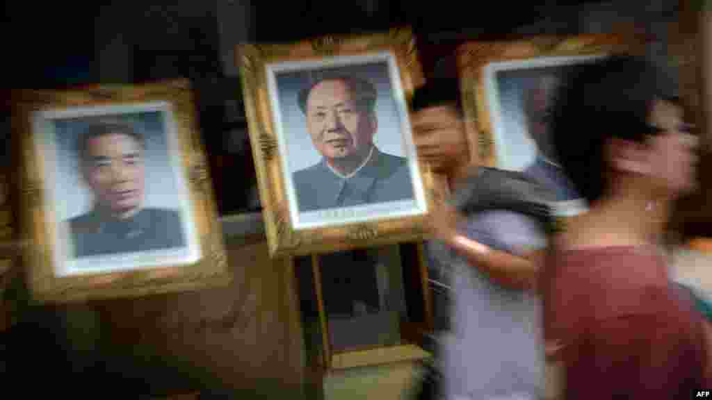 Pedestrians walk past portraits of past Chinese leaders as Beijing prepares for the 18th National Congress of the Communist Party that will see a change in the country's leadership. (AFP PHOTO/Mark Ralston)