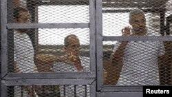 """""""Әл-Жазира"""" телеарнасының журналистер (солдан оңға) Бахир Мухаммад, Питер Грист пен Мохамед Фахми сотта отыр. Каир, 1 маусым 2014 жыл."""