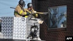Policia thyen xhamin e dritares së apartamentit të Xhejms Holmsit, ku u gjet armatim...