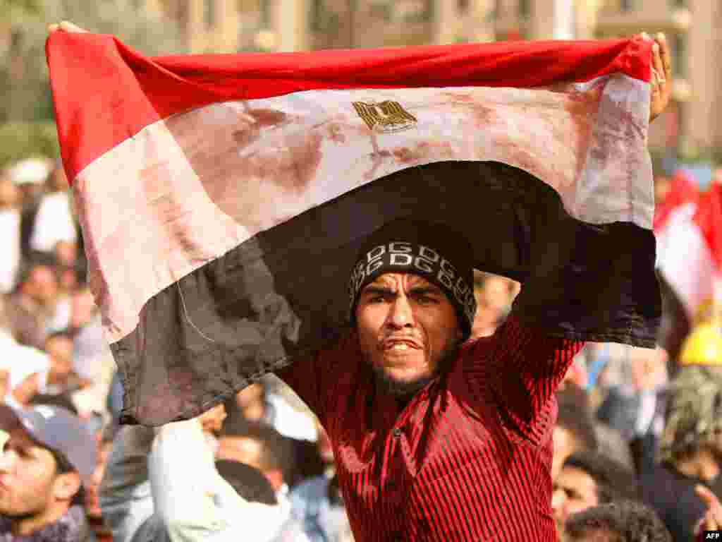 An antigovernment protester waves a bloodstained Egyptian flag in Cairo's iconic Tahrir Square on February 4. (AFP/Khaled Desouki)