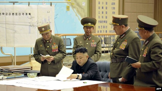 North Korean leader Kim Jong Un (seated) is seen in an official handout photo reportedly discussing a strike plan with North Korean officers during an urgent operation meeting at the Supreme Command in an undisclosed location.