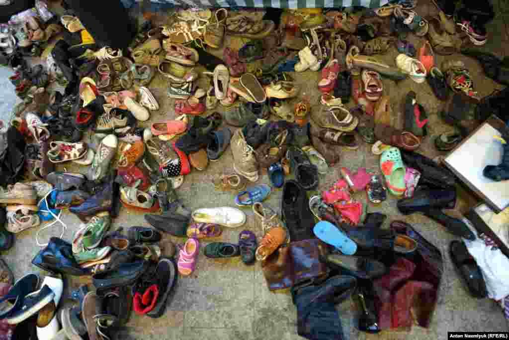Взуття на купу звалене на підлозі, його можуть взяти, хто захоче