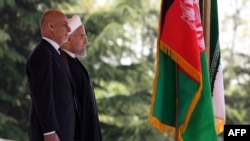 Visiting Afghan President Ashraf Ghani (left) and Iranian President Hassan Rohani at a welcoming ceremony in Tehran on April 19