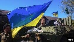 Ushtari ukrainas e mbanë flamurin e dëmtuar kombëtar në një pozicion në pjesën lindore të Ukrainës