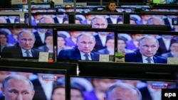 TV screens showing Russian President Vladimir Putin during an annual nationwide Q&A on April 16.