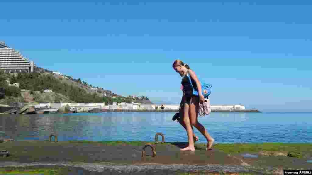 Подростки после купания и ныряния с пирса осторожно возвращаются по скользкой поверхности