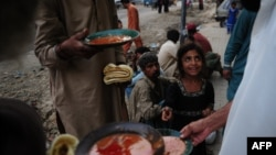 Pakistani residents eat food given out by a charity outside a restaurant in Karachi, April 8, 2016.