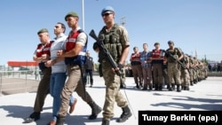 Soldiers who are charged with participating in the 2016 attempted coup in Turkey are accompanied by Turkish soldiers as they arrive at the court outside Ankara on August 1.