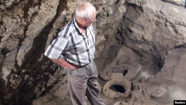 Armenia -- Archaeologist Levon Petrosian looks at a 6,100-year-old wine-making equipment discovered by an international project at the excavations of the Areni-1 cave complex, undated