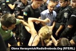 Працівники спецпідрозділу «Грифон» виводять з зали суду дівчину за порушення порядку