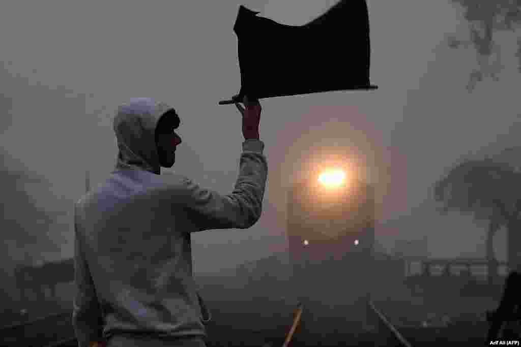 A signalman waves a flag as a train approaches at a station on a cold and foggy morning in Lahore, Pakistan. (AFP/Arif Ali)