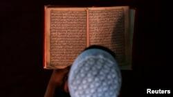 Молодой мусульманин за чтением Корана. Иллюстративное фото.