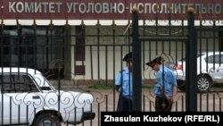 Қылмыстық-атқару жүйесі комитеті ғимараты қақпасы алдында тұрған полицейлер.