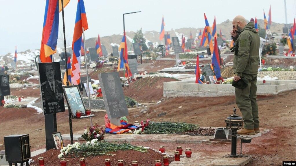 مردی بر سر مزار یکی از سربازان ارمنی کشته شده در جنگ اخیر قرهباغ دعا میخواند
