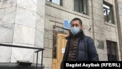 Активист Альнур Ильяшев на фоне здания территориальной избирательной комиссии.