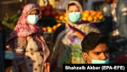 People wearing face masks walk through a market in Karachi. (file photo)