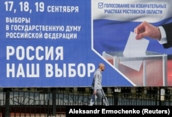 A man walks past a billboard informing residents of the Russian parliamentary elections on a street in the rebel-held city of Donetsk.