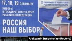 Потенційний виборець проходить повз плакат про майбутні вибори до парламенту Росії на вулиці в окупованому Донецьку, 9 вересня 2021 року