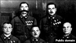 Маршалы сидят (слева направо): М.Н. Тухачевский, К.Е. Ворошилов, А.И. Егоров; cтоят: С.М. Буденный и В.К. Блюхер. 1935