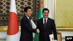 Жапония премьер-министрі Синдзо Абэ (сол жақта) және Түркіменстан президенті Гурбангулы Бердімұхамедов қол алысып тұр. Ашғабат. 23 қазан 2015 жыл.