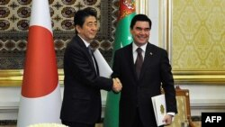 Turkmen President Gurbanguly Berdymukhamedov, right, shakes hands with Japanese Prime Minister Shinzo Abe during a signing ceremony following their meeting in Ashgabat on October 23.