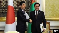 Turkmen President Gurbanguly Berdymukhamedov (right) shakes hands with Japanese Prime Minister Shinzo Abe following their meeting in Ashgabat on October 23.