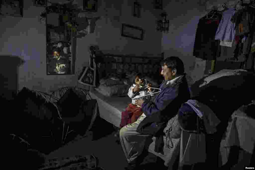 A man plays with his son as he sits in his one-room home in a Christian slum in Islamabad, Pakistan. (Reuters/Zohra Bensemra)