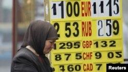 Женщина просит милостыню у обменного пункта в Киеве.