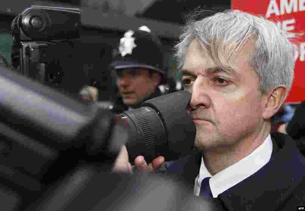 Британиялъул вукlарав экономикаялъул министр Крис Хьюнил могlрода тункараб фотографасул камера. (AFP/Justin Tallis)