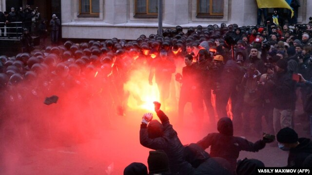 Protesters clash with riot policemen outside the Ukrainian President's office in Kyiv.
