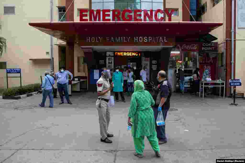 Роднините на едно лице кое е заболено од ковид-19 се расправаат со полицаец дапред една од болниците во Њу Делхи, 1 мај 2021 година.