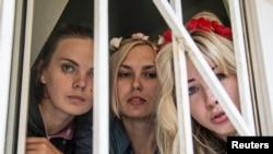 Три задержанные активистки FEMEN выглядывают из окна суда в Киеве. 28 июля 2013 года