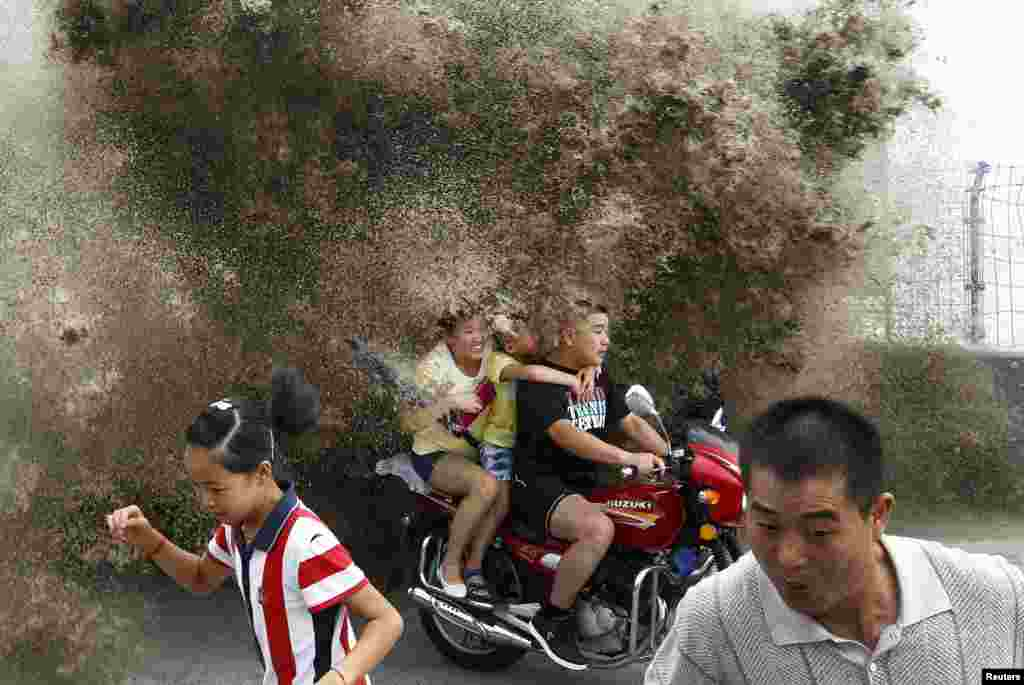 Visitors flee as waves caused by a tidal bore surge past a barrier on the banks of Qiantang River, in Hangzhou, in China's Zhejiang Province. (Reuters)
