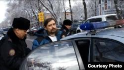 Полиция сажает в машину задержанного блогера Дмитрия Щелокова. Алматы, 21 февраля 2014 года.