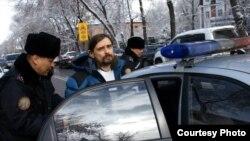 Полицейские сажают в патрульный автомобиль задержанного блогера Дмитрия Щелокова. Алматы, 21 февраля 2014 года.