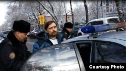 Полиция блогер Дмитрий Щелоковты көлікке отырғызып жатыр. Алматы, 21 ақпан 2014 жыл.