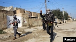 Gunmen walk in the streets of the Iraqi city of Ramadi, 100 kilometers west of Baghdad, in January.