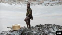 Нигерийский мальчик ловит рыбу на загаженном нефтью берегу вблизи города Гой. Иллюстративное фото.