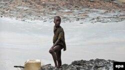 Гой қаласы маңында мұнайдан ластанған су жағасында балық аулап тұрған нигериялық бала. (Көрнекі сурет.)