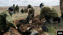 Волонтеры раскапывают могилу украинского солдата.