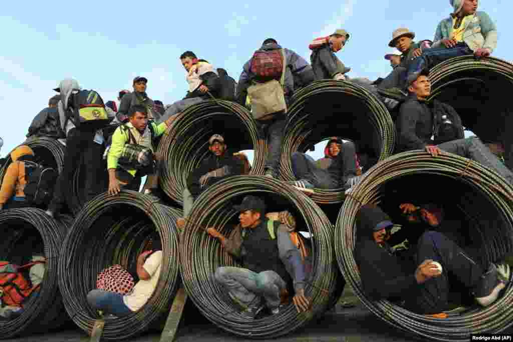 Central American migrants, part of the caravan hoping to reach the U.S. border, get a ride on a truck carrying rolls of steel rebar in Irapuato, Mexico, on November 12.(AP/Rodrigo Abd)