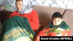 Жители села Акжол - пенсионерка Гульмира Сагиева со своим 8-летним внуком Арматом. ЗКО, 3 февраля 2015 года.