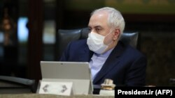 Iranian Foreign Minister Mohmmad Javad Zarif wears a protective mask and gloves as means of protection against the cornonavirus COVID-19, during a cabinet meeting in the capital Tehran, March 11, 202
