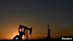 Домкрат-насос работает перед буровой установкой на закате на нефтяном месторождении в Мидленде, штат Техас, США, 22 августа 2018 г.