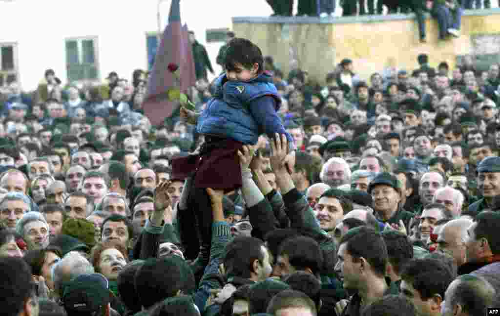 Supporters of the opposition hold up a little girl holding a flower during a rally in front of the presidential residence in Tbilisi on November 22. Georgia teetered on the brink of chaos, with Shevardnadze declaring a state of emergency and an opposition leader claiming the interim presidency after supporters overran parliament.