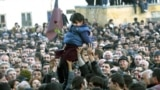 Supporters of the opposition hoist a small girl holding a flower during a rally in front of the Georgian presidential residence in Tbilisi on November 22, 2003.