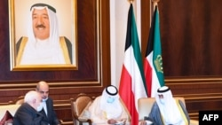 Kuwait's new Emir Sheikh Nawaf al-Ahmad Al-Sabah (R) receiving condolences from Iranian Foreign Minister Mohammed Javad Zarif (L) in Kuwait City.